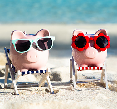Two piggy banks on the beach wearing sunglasses