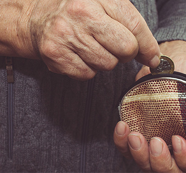 Senior man adding a coin to a small coin purse