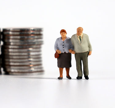 Clay figurine couple standing next to stacks of nickels