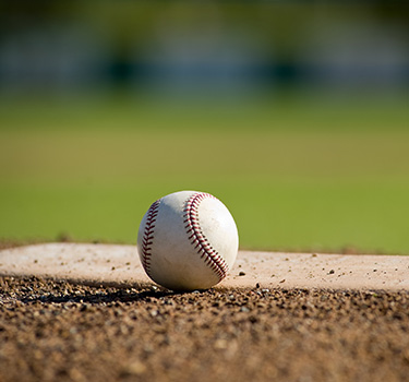 Close up photo of a baseball sitting next to the pitcher's mound